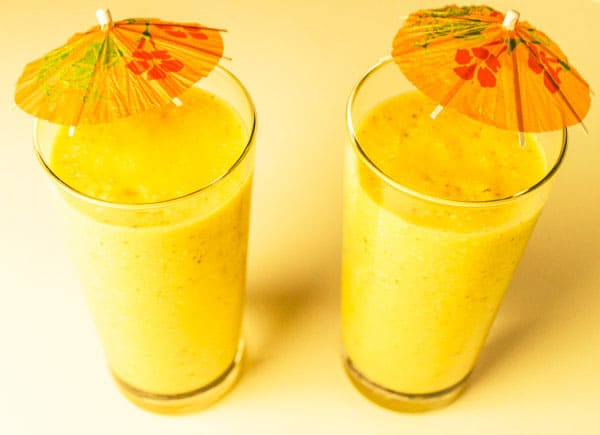 Caribbean Sunshine Smoothie packed with Vitamin C, made with Coconut Milk, Mango, Pineapple, Banana, Coconut Flakes, and Chia Seed Gel. by Tastefulventure.com