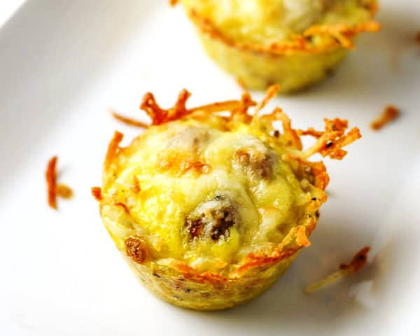 These Sausage Egg and Cheese Hash Brown Cups are so easy to make! Just layer everything in a muffin tin and bake, perfect for breakfast on the go! | Tastefulventure.com