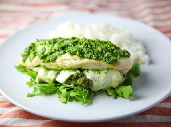 This Baked Chicken stuffed with Arugula Pesto and Mozzarella is super easy to make and loaded with flavor! This will be your new favorite easy weeknight meal!