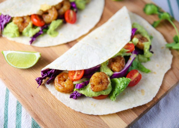 These Spicy Shrimp Tacos with Avocado Cilantro Sauce are totally addicting and loaded with flavor!