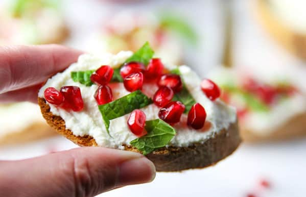 This Pomegranate Crostini with Ricotta and Mint will be your new favorite appetizer! It's super easy to make for any last minutes guests, and is sure to wow a crowd!