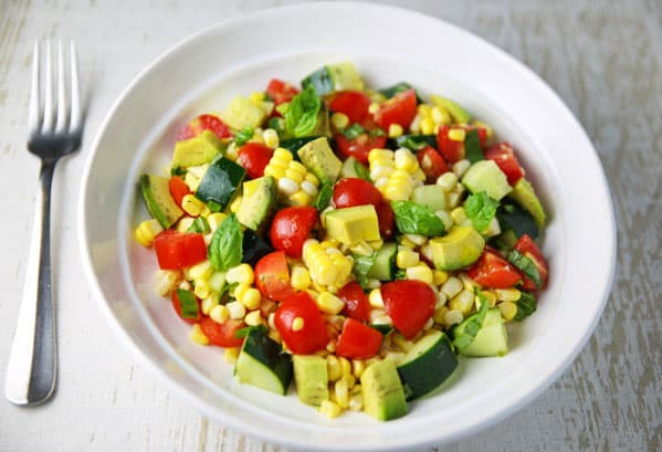 This Avocado Corn Tomato and Cucumber Salad is the perfect summer dish! Eat it as a meal or as a side!