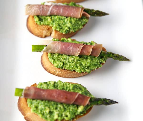 These Prosciutto Wrapped Asparagus with Lemon Pesto Crostini are a great appetizer to throw together at the last minute. This is a hit at every party! #appetizer #glutenfree #prosciutto #asparagus #easyrecipes