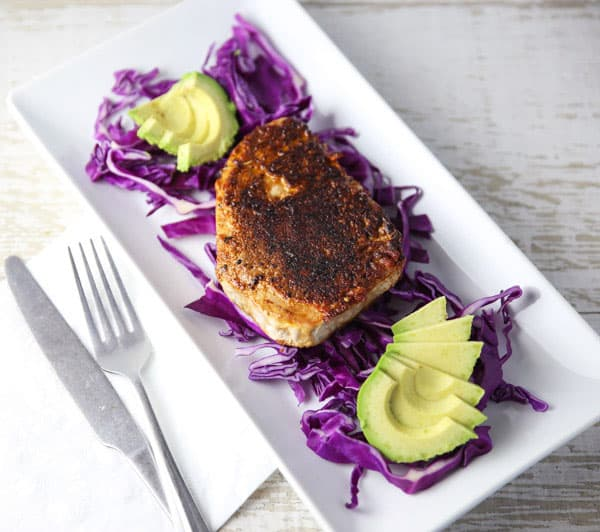 Blackened Tuna Steaks on a bed of red cabbage with avocado