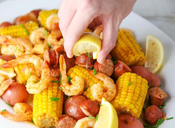 squeezing lemon on shrimp boil