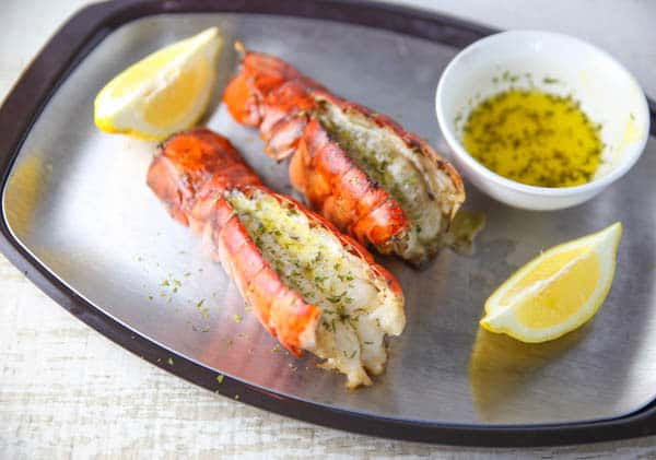 lobster tails oon a platter with lemon and butter