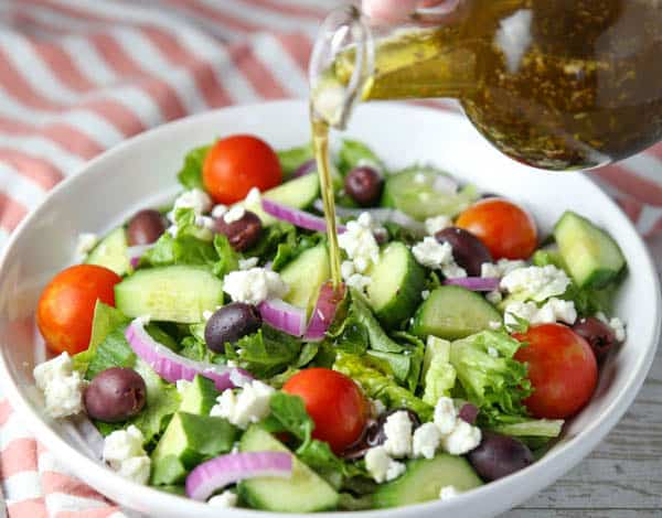 Homemade Greek Salad Dressing being poured on the salad