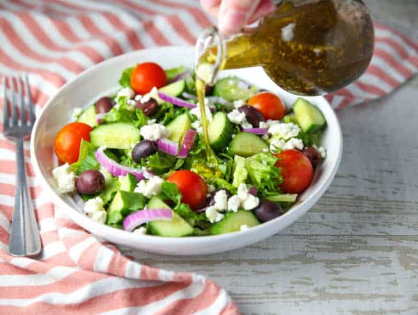 Homemade Greek Salad Dressing pouring on the salad in a bowl